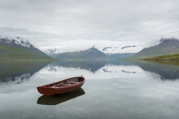 Iceland fjord with red wooden boat
