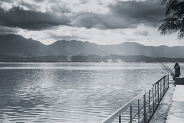 fisherman fishing at quiet lake with mountain sky and cloudy countryside black and white tone.