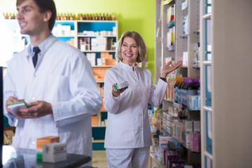 Two pharmacists posing in drugstore