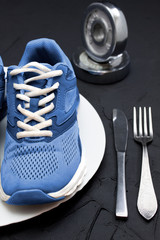 Sport shoes on wtite plate, fork and knife.