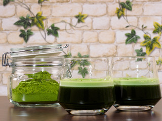 Two glasses of green juice and a jar of green juice powder