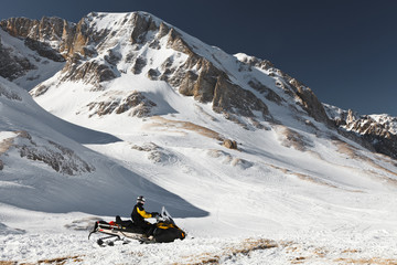 A man on a snowmobile against a background of snowy mountain peaks. State Nature Reserve in Adygea, Russia.