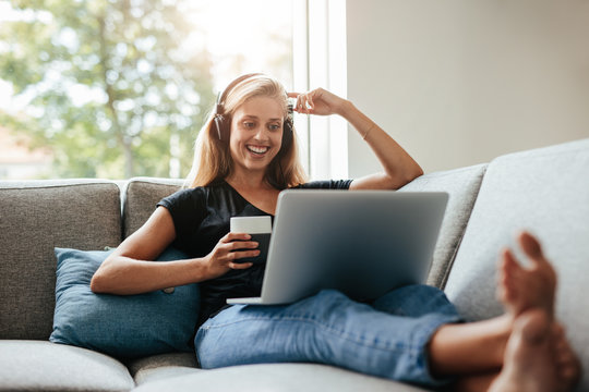 Smiling woman relaxing in living room with laptop
