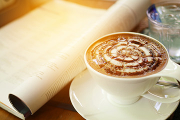 Cup of mocha with newspaper on the table, coffee shop background