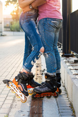 Legs wearing inline skates. Couple in jeans. Fashion and sport.