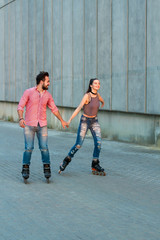 Woman and man rollerblading. Couple holding hands and smiling. Live to move.