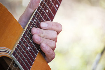 closeup of man's hands playing acoustic guitar, soft vintage sty