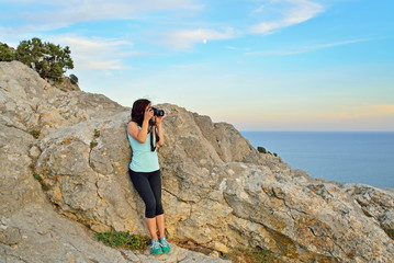 Girl tourist photographing the landscape at sunset