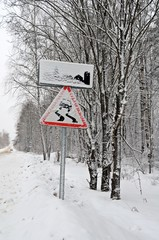 """Дорожные знаки """"Изображение населенного пункта"""" и """"Скользкая дорога"""",  заметенные снегом."""
