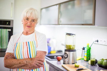 Senior woman/grandmother cooking in a modern kitchen