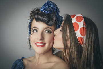 Fashionable young women having friendly kiss