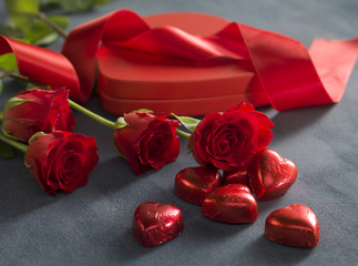 red hearts chocolates in front of red roses and hart shaped box