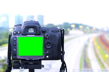 Digital single-lens reflex camera with green screen display stand on tripod