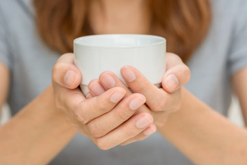 Woman hands holding coffee cup.