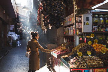 Woman chooses in the market nuts and dried fruit, the buyer trie