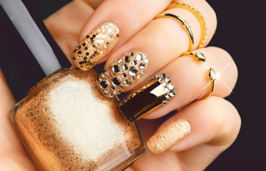 Golden nail art manicure. Holiday style bright manicure with gems and sparkles. Bottle of nail Polish. Fashion rings