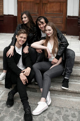 Young elegant trendy friends outdoors, wearing black and white clothing