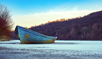 Blue fishing boat on a frozen lake.