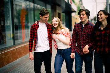 Four happy trendy teenage friends walking in the city, talking each other and smiling. Lifestyle, friendship and urban life concepts.