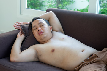 un-wear shirt fat asian man sleeping on the couch at home