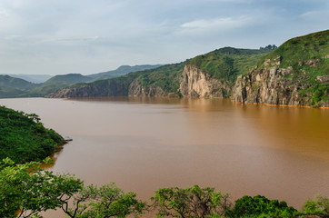 Landscape including calm brown water of Lake Nyos, famous for CO2 eruption with many deaths, Ring Road, Cameroon