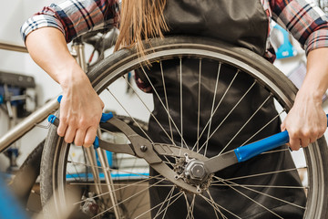 Hardworking craftswoman fixing the chain of the bicycle