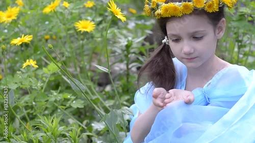 Little girl in wreath of dandelions sitting in the grass