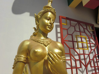 Thai golden statue touching breast