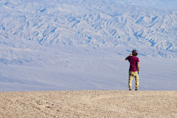 One young man takes a photo in the desert with a smartphone, staring at the horizon from the edge of the valley. He stands against a blue hue mountain texture, lighted by soft light.