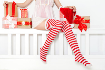 Sexy woman in lingerie and sexy Santa stockings with gifts and Christmas caps. Xmas. Christmas sale. Shopping