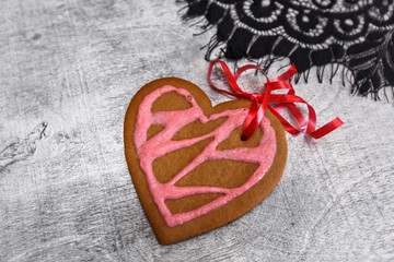 Chocolate gingerbread cookies heart shaped with red and pink icing on white plate