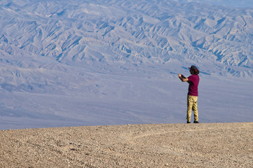 One young man takes a pictures in the desert with a smartphone from the edge of the valley. He stands against a blue hue mountain texture, lighted by soft light.