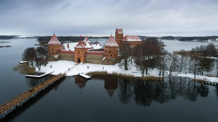 Trakai, Lithuania: aerial winter UAV top view, flat lay of Island Castle in the sunrise. Historical residence in capital city of Grand Duchy of Lithuania, located in Galve lake