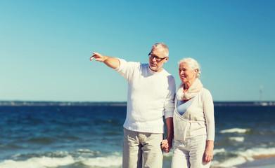 happy senior couple walking on summer beach