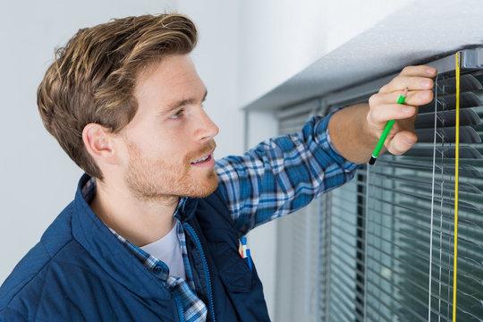 Contractor measuring venetian blinds