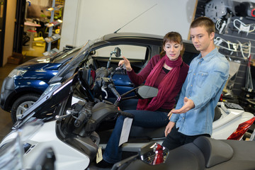 Young man and woman in vehicle showroom