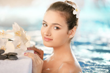 Spa vacations concept. Young woman relaxing in swimming pool