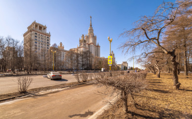Tilt and shift view wide angle view of long avenue of spring sunny campus of Moscow university with a car