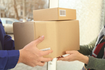 Courier giving parcels to customer, closeup