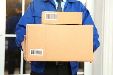 Courier with parcels on doorstep, closeup