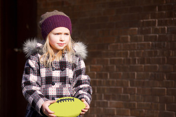 adorable school age girl holding football