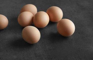 Raw eggs on color background