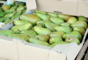 Cardboard box with juicy pears on market