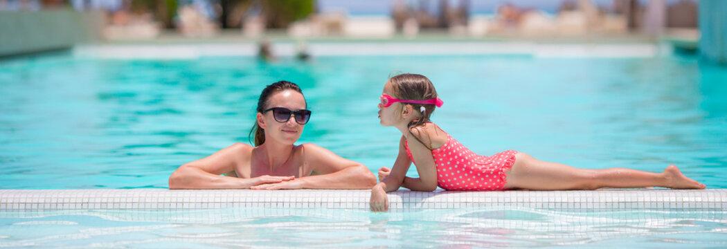 Family enjoying summer vacation in luxury swimming pool