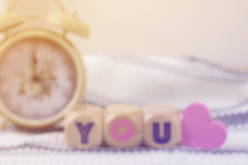 blurry picture of lovely wood blocks with vintage alarm clock for valentine background, filtered tones