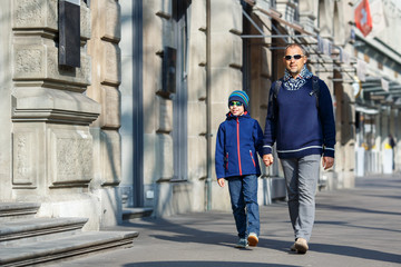 Father and son walking in city