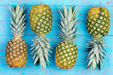 Four alternating pineapples on market table