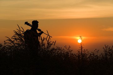 Silhouette of a young who like to travel and photographer, takin