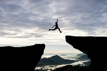 Man jump through the gap between hill.man jumping over cliff on sunset background,Business concept...