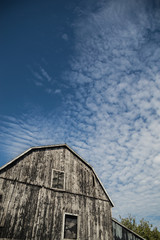 Gambrel roof black weathered barn with deep blue sky and cloudsc